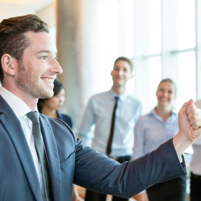 Cheerful leader motivating his business team. Handsome young politician telling his plan and showing fist as symbol of power. Positive business people standing in background. Strong company concept